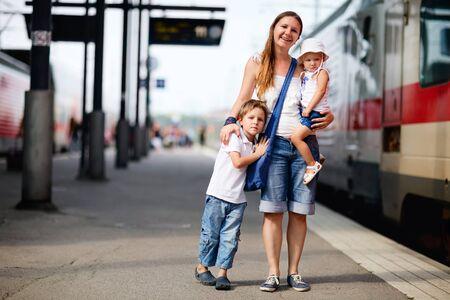 estacion tren: Joven madre y dos ni�os esperando el tren sobre la plataforma de la estaci�n de ferrocarril  Foto de archivo