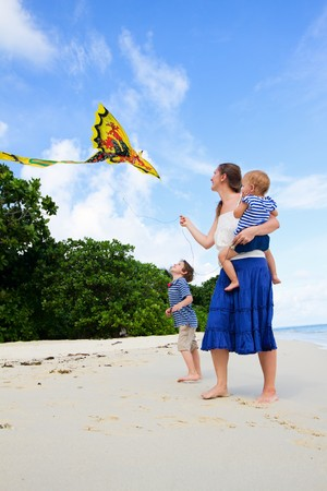 Mother and her two kids flying kite on white sand tropical beach photo