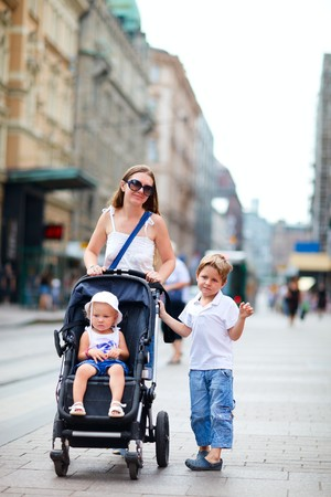 buggy: Vertical photo of mother with her son and toddler daughter in stroller walking in city center