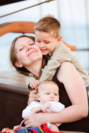 Vertical portrait of loving mother and two adorable kids photo
