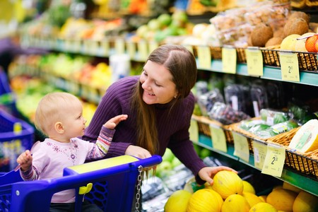 happy family shopping: Young mother and her adorable baby daughter selecting fruits in supermarket