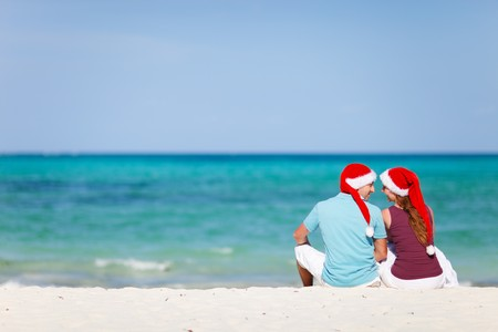 Back view of young romantic couple in red Santa hats sitting on beach and looking to each other photo
