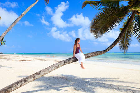 Young lady sitting on palm tree at tropical beach photo