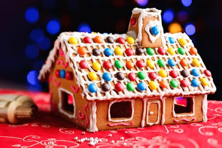 Gingerbread house decorated with colorful candies over Christmas tree lights background photo