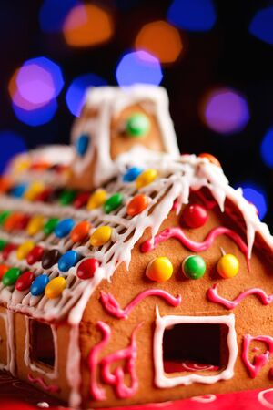 Closeup of beautiful gingerbread house over Christmas tree lights background photo