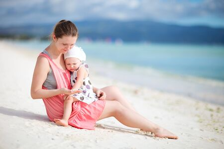 Young mother and her little daughter sitting on tropical beach photo