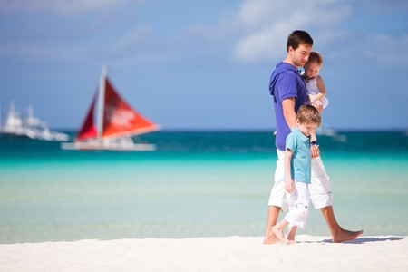 Young father and his two kids walking along tropical beach photo