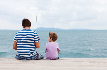 sea fishing: Back view of father and son fishing together from jetty Stock Photo