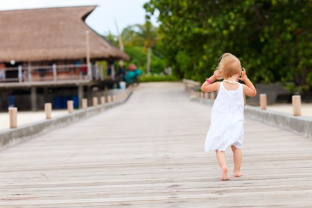 Back view of toddler girl running on jetty photo