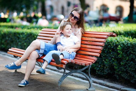 mother on bench: Happy mother and son sitting on bench in city park on summer day Stock Photo
