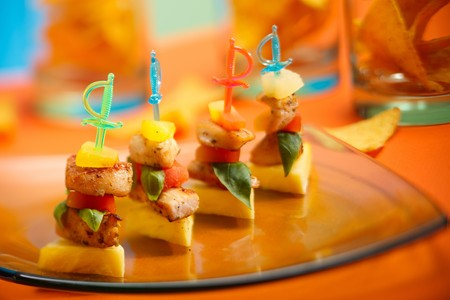 Party appetizers on colorful sticks served on platter photo
