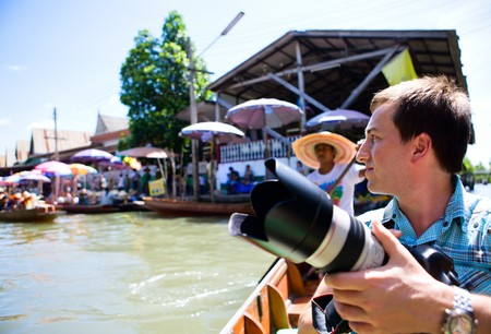Photographer at exotic floating market near Bangkok in Thailand photo