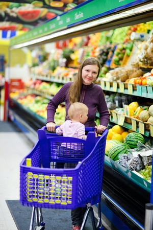 Vertical photo of young mother and her baby daughter shopping in supermarket photo