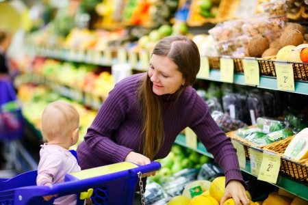 Mother and baby daughter in supermarket buying fruits photo
