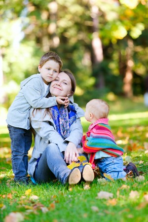 Mother and two kids sitting on grass at sunny autumn day photo