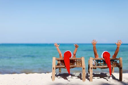 Happy romantic couple in red Santa hats at tropical beach relaxing on sun beds photo