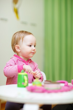 Vertical portrait of cute toddler girl playing with toys at home or daycare place photo