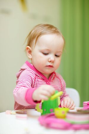 Portrait of cute toddler girl playing with colorful wooden toys at home or daycare place photo