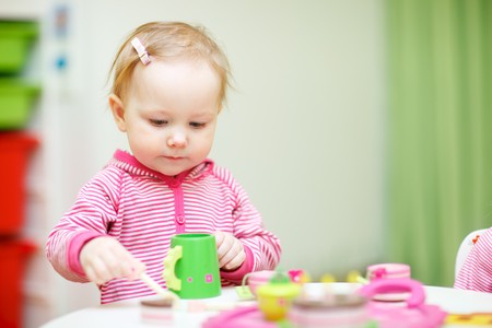 Adorable toddler girl playing with wooden teapot and cups  at home photo