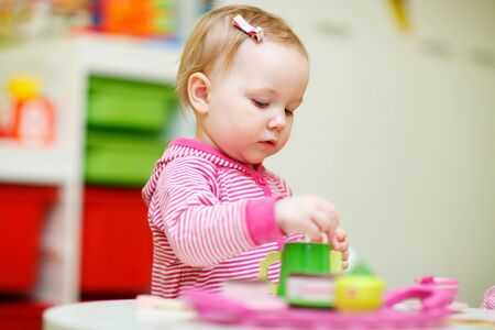 Adorable toddler girl playing with toys at home or daycare place photo