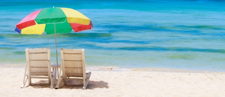 Panoramic photo of tropical beach with two chairs and colorful umbrella photo