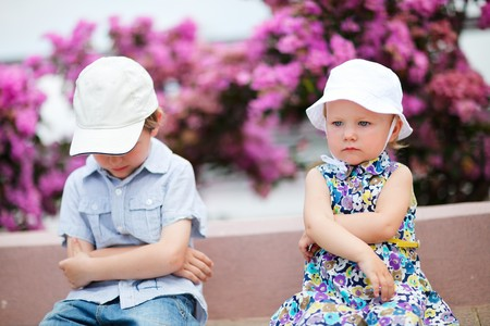 little boy and girl: Two upset kids sitting outdoors in city