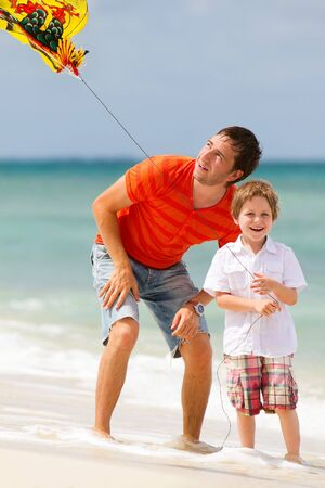 kite flying: Portrait of happy dad and son flying kite together