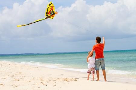 padre e hijo: Vista de realizar la copia de seguridad si feliz papá e hijo volando juntos kite  Foto de archivo