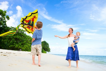 kites: Mother and two kids flying kite on tropical beach. Focus on boy Stock Photo