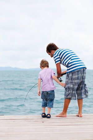 Vertical photo of father and son fishing from wooden jetty photo