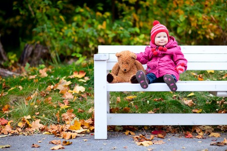Adorable toddler girl sitting on bench in autumn park photo