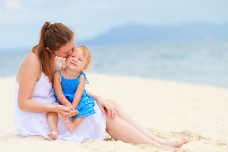 Young loving mother kissing her toddler daughter on white sand tropical beach photo