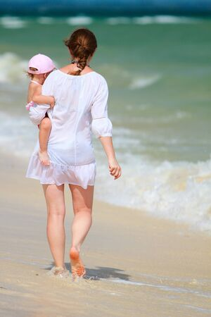 Rear view of young mother and her little daughter on tropical white sand beach photo