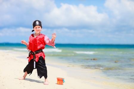 Cute boy dressed as pirate on tropical beach photo