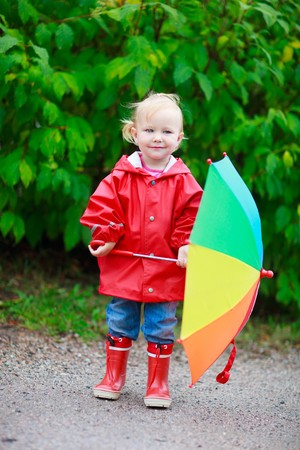 Full body portrait of adorable toddler girl with colorful umbrella outdoors on rainy day photo