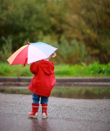 botas de lluvia: Ni�a adorable ni�o peque�o con coloridos paraguas al aire libre en el d�a de lluvia de oto�o