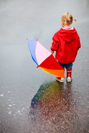 toddler walking: Toddler girl with colorful umbrella outdoors at rainy day