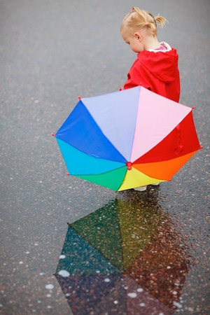 rainy day: Toddler girl with colorful umbrella, beautiful reflection on wet ground