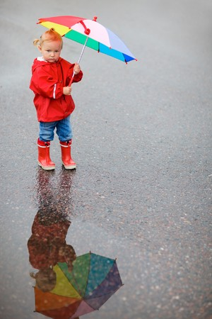 rainy day: Toddler girl with colorful umbrella, beautiful reflection on puddle Stock Photo