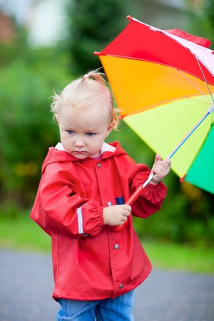 Portrait of adorable toddler girl with colorful umbrella outdoors on rainy day Stock Photo - 7819671
