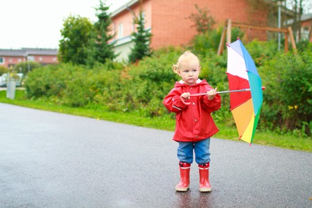 Adorable toddler girl with colorful umbrella outside on rainy day Stock Photo - 7819650