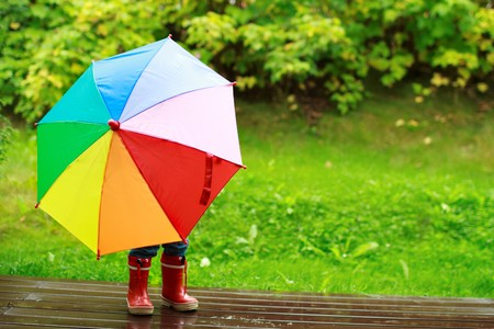 umbrella rain: Playful little girl hiding behind colorful umbrella outdoors