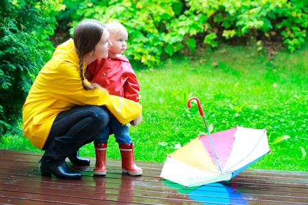 botas de lluvia: Joven madre y su peque�a hija al aire libre en coloridos impermeables