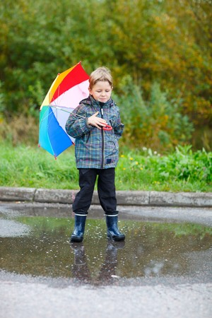 Cute boy with colorful umbrella outdoors at autumn rainy day photo