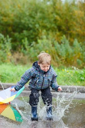 botas de lluvia: Niño juguetón saltando en charco lluvioso día de otoño