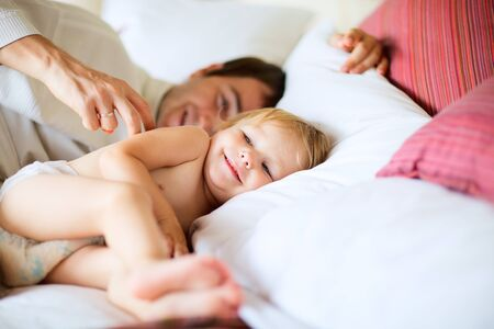 Happy father and his little daughter playing in bedroom photo