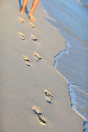 Vertical photo of footprints closeup on white sand tropical beach photo
