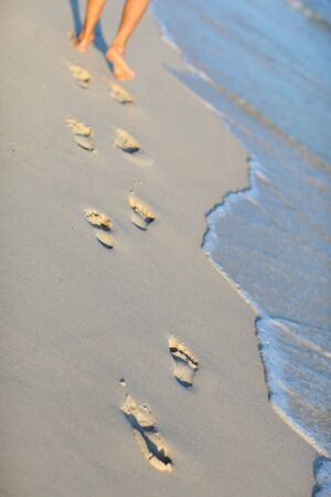 Vertical photo of footprints closeup on white sand tropical beach photo