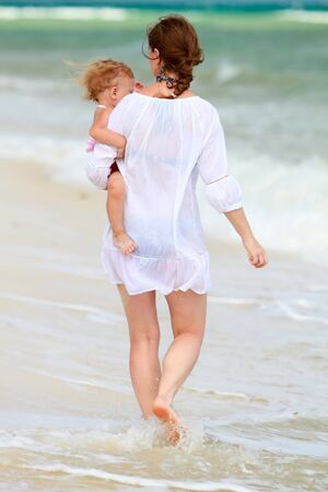 Rear view of mother holding baby in her hands walking along shore photo