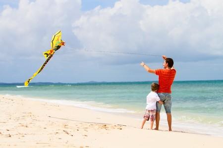 父と息子のビーチでカイトを飛行の背面図 写真素材